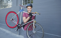 Portrait smiling young man carrying bicycle on urban sidewalk - CAIF12209