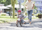 Mother chasing son riding bicycle with helmet in sunny park - CAIF12212