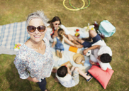 Portrait smiling senior woman with family at picnic - CAIF12221