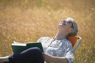 Senior woman reading book and laughing with head back in sunny field - CAIF12233