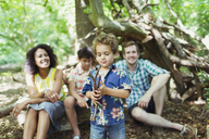 Family watching boy play with sticks in woods - CAIF12269