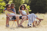 Smiling family relaxing in sunny field - CAIF12320
