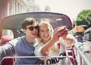 Couple taking selfie on double-decker bus in London - CAIF12329