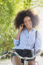 Enthusiastic woman with afro riding bicycle listening to music on headphones - CAIF12335
