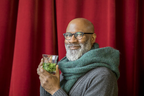 Portrait of happy man with glass of tea - FMKF04912
