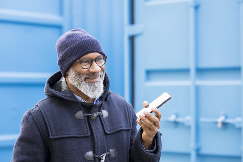 Portrait of smiling man using cell phone outdoors - FMKF04915