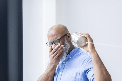 Laughing businessman with tin can phone in the office - FMKF04921