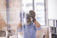 Portrait of businessman with Virtual Reality Glasses and boxing gloves in the office - FMKF04936