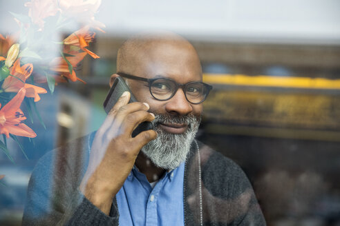 Portrait of smiling man on the phone behind windowpane - FMKF04942