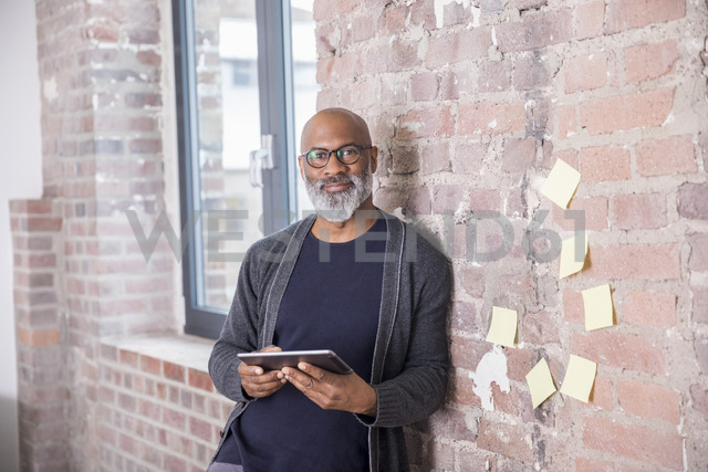 Portrait of smiling freelancer with tablet leaning against wall in a loft - FMKF04951 - Jo Kirchherr/Westend61