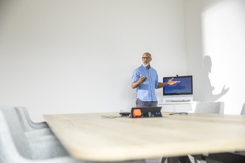 Businessman in conference room leading a presentation - FMKF04957