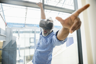 Businessman wearing VR glasses at the window - FMKF04963