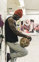 Man with tattoos and woolly hat holding basketball - UUF12986
