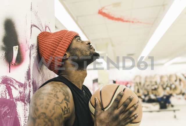 Man with tattoos and woolly hat holding basketball - UUF12989