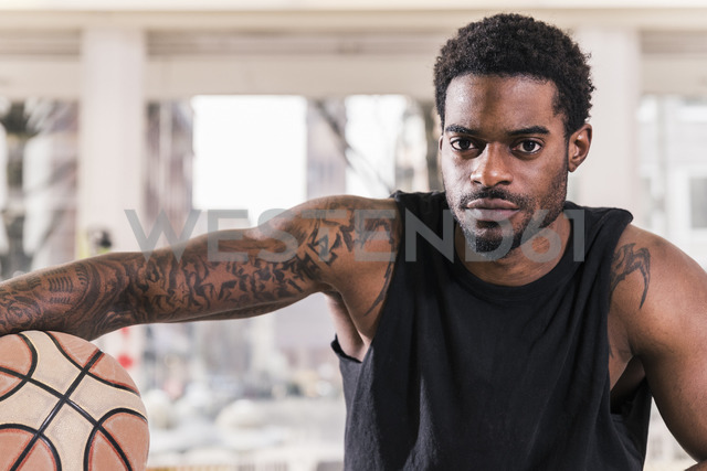 Portrait of confident man with tattoos holding basketball - UUF12995