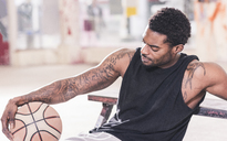 Man with tattoos sitting down holding basketball - UUF12998