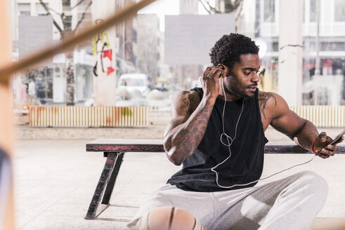 Man with tattoos and basketball using smartphone and earphones - UUF13001