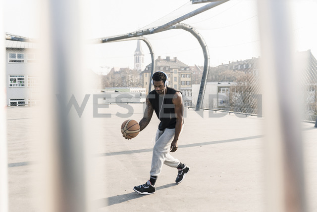 Basketball player with headphones in action on court - UUF13013