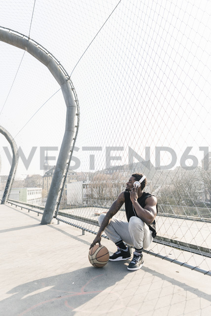 Basketball player on court crouching at fence listening to music - UUF13019