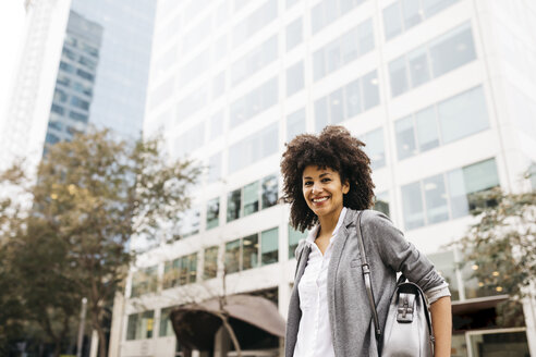 Portrait of smiling woman with bag  outdoors - JRFF01613
