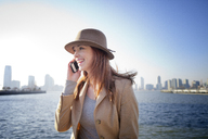 Woman talking on mobile phone against river in city - CAVF05601