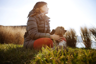 Low angle view of woman with dog sitting on field against clear sky - CAVF05613