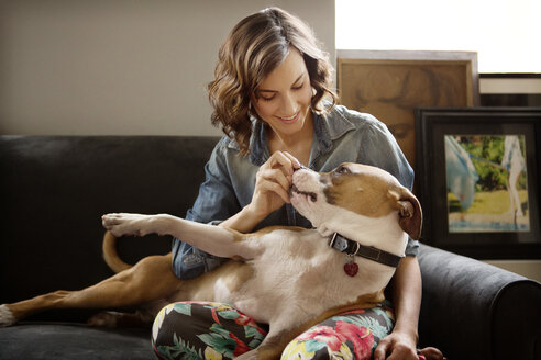 Woman playing with dog at home - CAVF05616