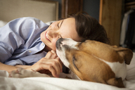 Playful woman with dog on bed at home - CAVF05622