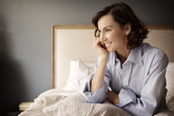 Woman with hand on chin looking away while sitting on bed at home - CAVF05625