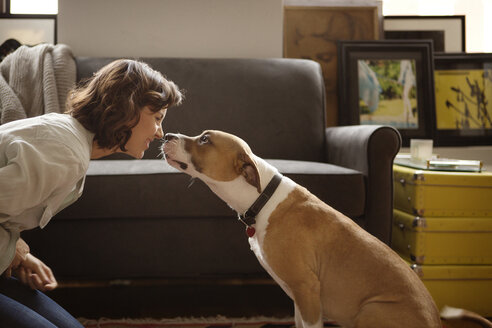 Woman rubbing nose with dog at home - CAVF05628
