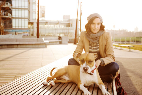 Portrait of woman with dog sitting on bench - CAVF05634
