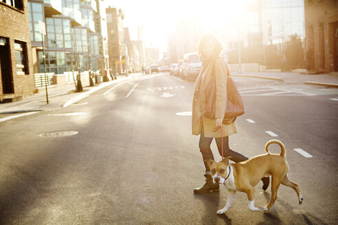 Side view of woman with dog crossing road in city - CAVF05637
