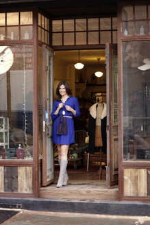 Portrait of woman standing at entrance in store - CAVF05814