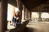 Portrait of woman sitting on retaining wall - CAVF05826