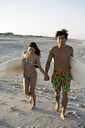 Couple with surfboards holding hands while walking on shore at beach - CAVF05889