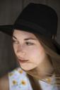 Woman wearing sun hat looking away against wood - CAVF06027