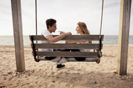 Side view of couple sitting on swing at beach - CAVF06048