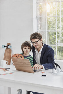 Businessman and son using laptop at desk - RORF01121