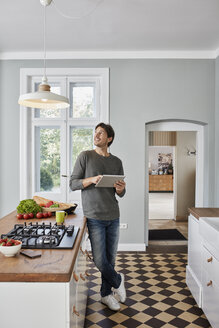 Man using tablet in kitchen looking at ceiling lamp - RORF01127