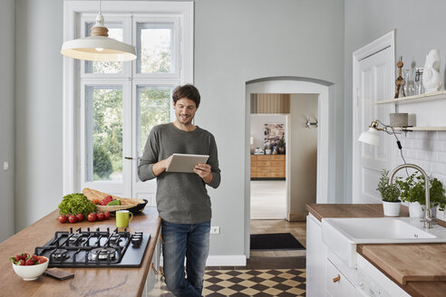 Smiling man using tablet in kitchen - RORF01130