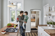 Happy father and son with bell pepper and tablet in kitchen - RORF01133
