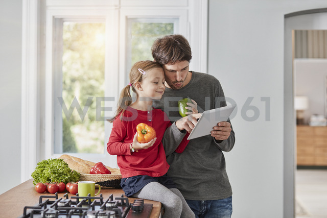 Father and daughter with bell pepper and tablet in kitchen - RORF01136 - Roger Richter/Westend61