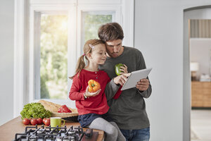 Father and daughter with bell pepper and tablet in kitchen - RORF01136