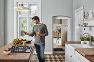 Smiling man using smartphone and holding bell pepper in kitchen - RORF01139