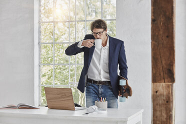 Businessman with skateboard drinking coffee and looking at laptop on desk - RORF01145