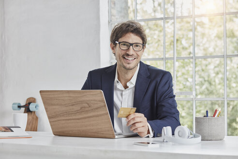 Portrait of smiling businessman with laptop on desk holding credit card - RORF01148