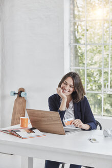 Smiling businesswoman using laptop on desk holding card - RORF01151