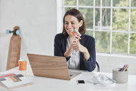 Happy businesswoman using laptop on desk holding card - RORF01157