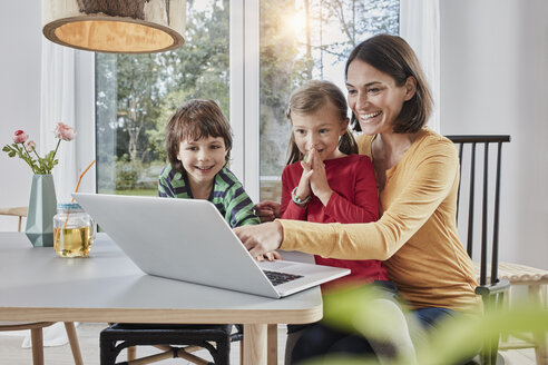 Happy mother with two children using laptop at home - RORF01160