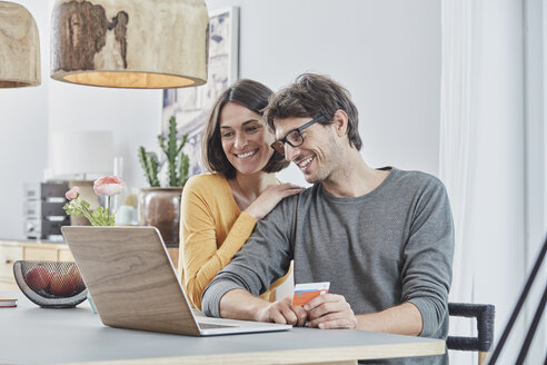 Happy couple with a card using laptop on table at home - RORF01166